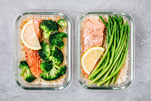 Meal prep lunch box containers with salmon, rice, broccoli, asparagus.