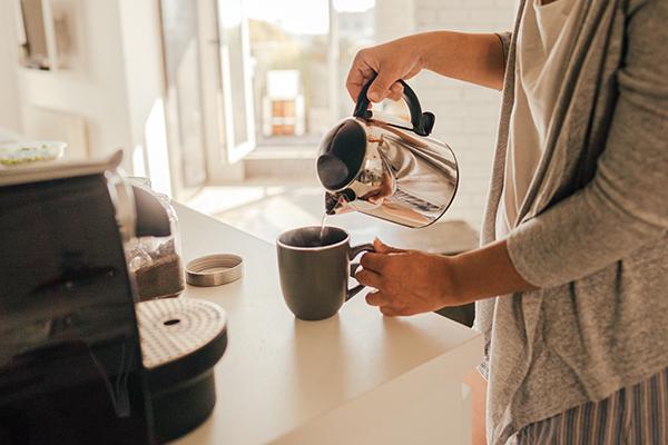 Woman making tea in her kitchen