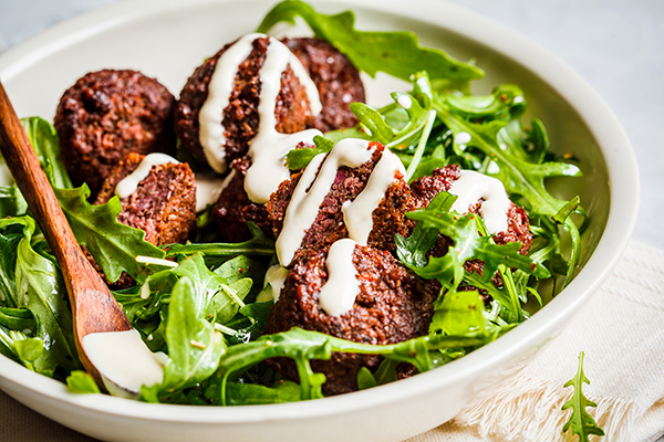 Falafel topped with tahini over greens