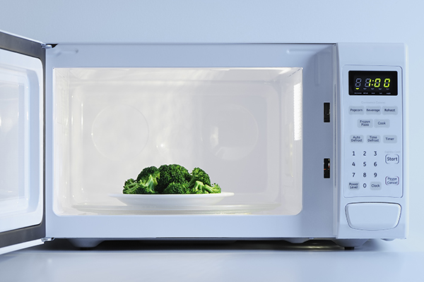 Plate of broccoli in a microwave.