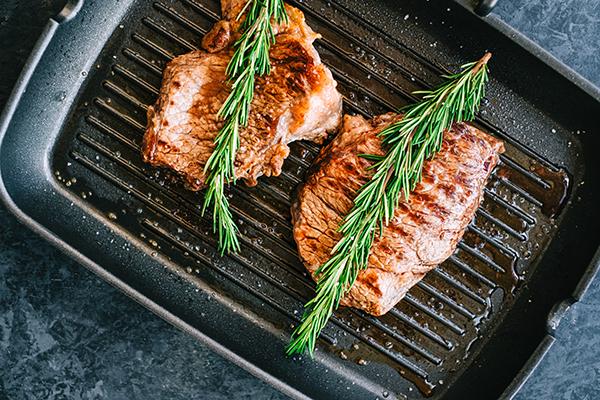 Bison meat steaks in frying pan