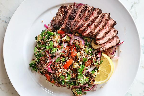 Sliced grilled steak with vegetables on plate