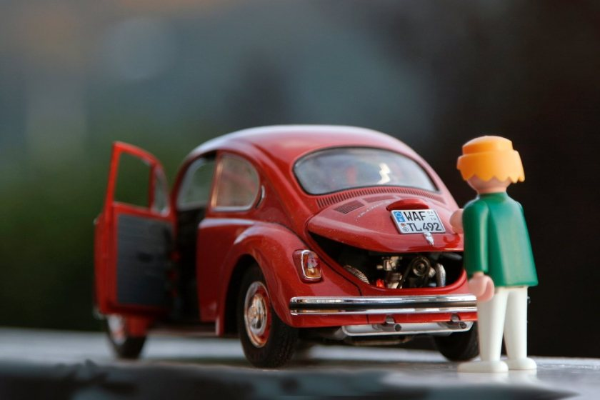 boneco conserta motor do fusca vermelho de brinquedo