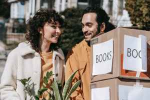 couple moving out carrying boxes and plants