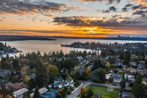 aerial view of houses near body of water during sunset