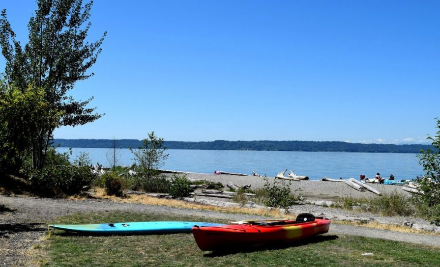 A kayak and a paddleboard on the beach at Seahurst Park in Burien WA