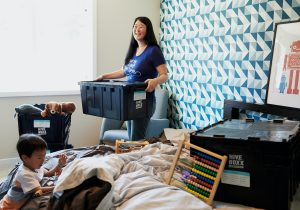 woman and child packing bedroom to move