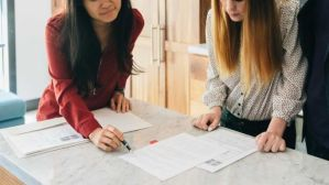 A real estate agent shows a home buyer a contract