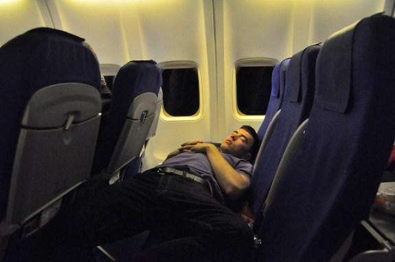 Man sleeping in economy class