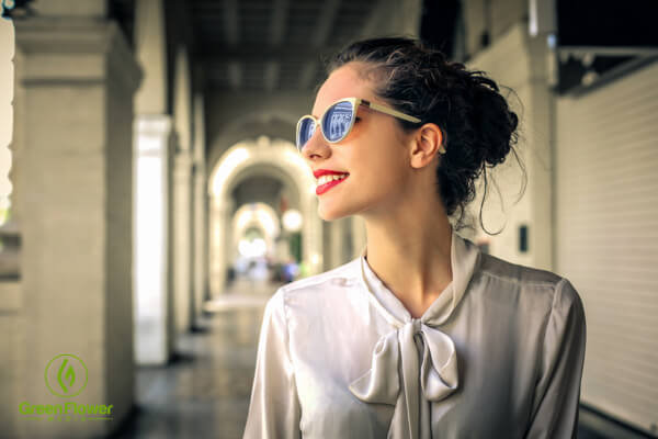 a happy woman outside with sunglasses