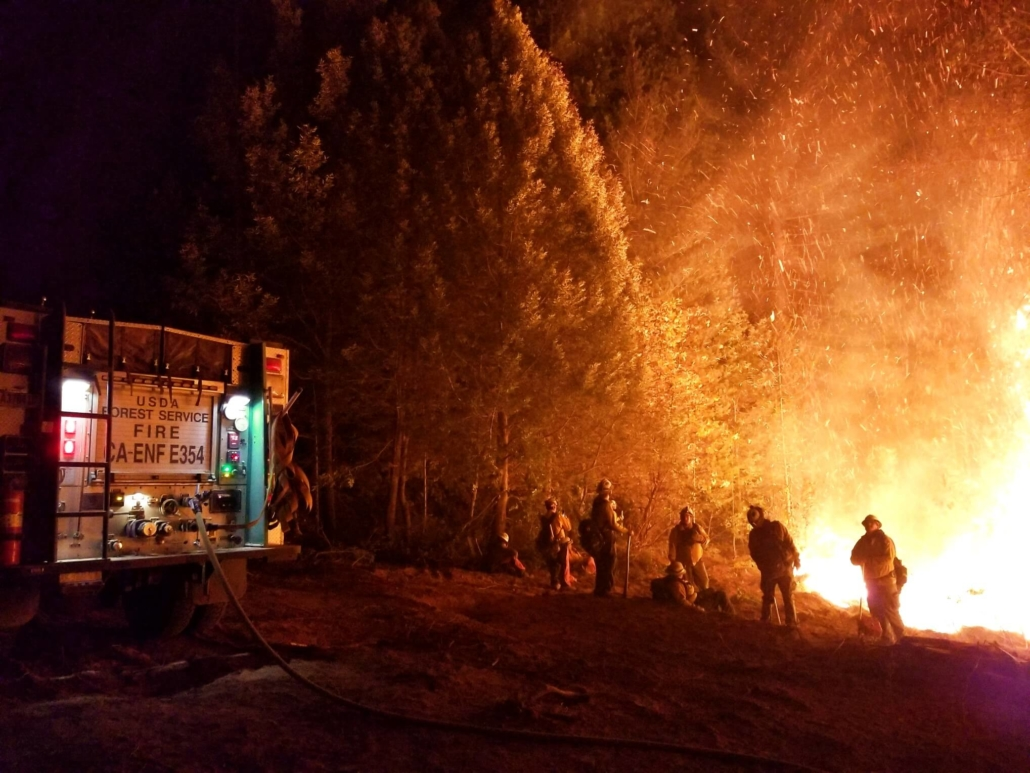 Firefighters fight camp fire