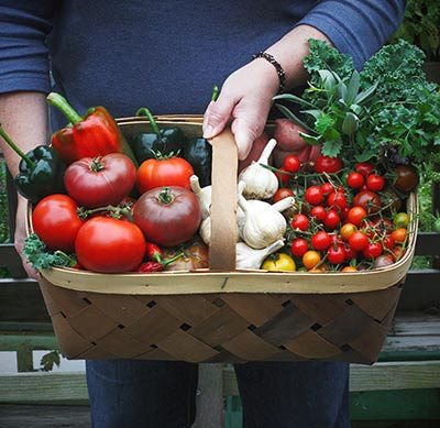 Karen Gibson holding a basket of harvest vegetables | SoupAddict.com