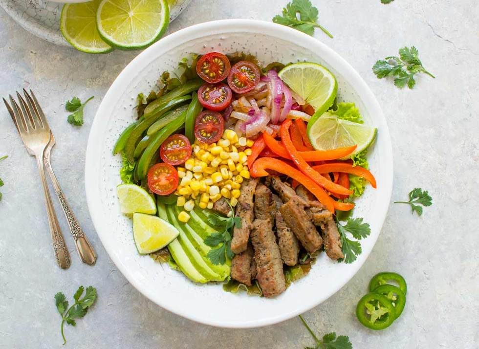Beef Fajita Salad with Creamy Salsa Dressing, served in a bowl. Recipe at SoupAddict.com
