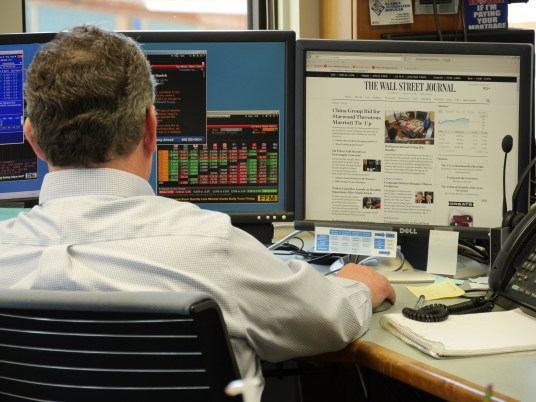 Chris Cummins, a senior portfolio manager at the Alaska Permanent Fund Corp., monitors a variety of economic information at his desk in the corporate headquarters, March 14, 2016. (Photo by Skip Gray/360 North)