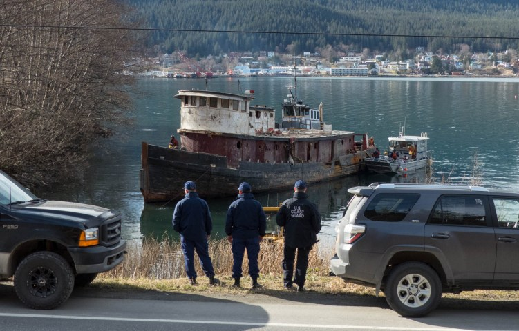 Members of the Coast Guard watch the tug Challenger moving into position to be beached and demolished on March 7, 2016 (Photo by David Purdy/KTOO)