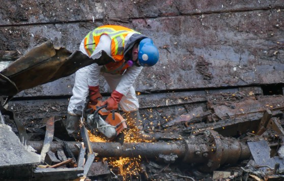 A worker cuts through a pipe on the tug Challenger on March 8, 2016 (Photo by David Purdy/KTOO)