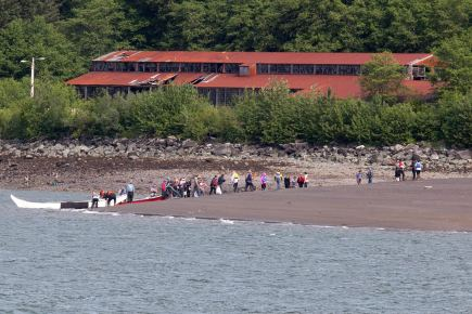 Members of the One People Canoe Society change into their regalia as they finish paddling the last leg of a trip from Angoon to Juneau on Wednesday, June 8, 2016, near Juneau, Alaska. The society began the trip on June 2. Their landing on Douglas Island is the unofficial beginning of Celebration. (Photo by Rashah McChesney/KTOO)