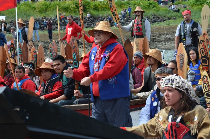 "John Martin asks for permission come ashore. He told the crowd, ""Today, we are practicing that our Tlingit, Haida, and Tsimshian people will come together. We will sing like one nation. We will speak like one nation. And we will dance like one nation."" (Photo by Emily Kwong/KCAW)"