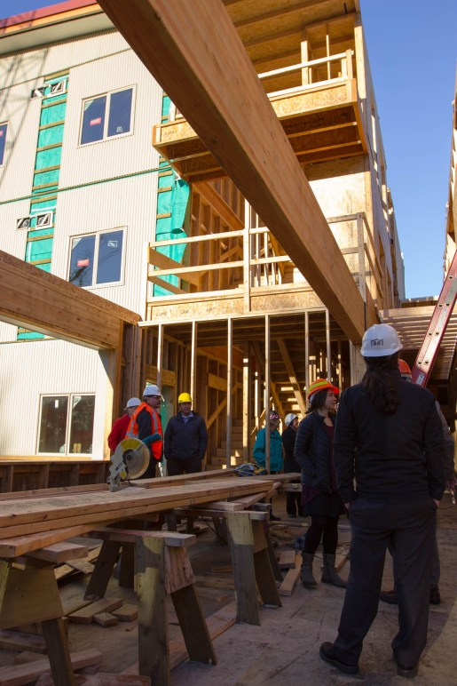 Stakeholders tour the construction of the in-progress Housing First Project on November 17, 2016. (Photo by David Purdy/KTOO)