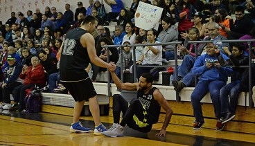 Angoon's John Croasman Jr. (12) helps Clayton Edwin (20) up after Edwin was fouled on a 3-point shot during their B-Bracket elimination game against Kake in the Juneau Lions Club 71st Annual Gold Medal Basketball Tournament at Juneau-Douglas High School on Wednesday. Angoon won 96-75. (Photo courtesy Klas Stolpe)