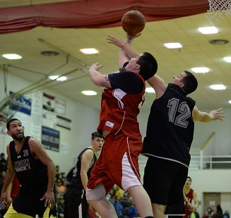 Kake's Deion Jackson is fouled by Angoon's John Croasman Jr. during their B-Bracket elimination game in the Juneau Lions Club 71st Annual Gold Medal Basketball Tournament at Juneau-Douglas High School on Wednesday. Angoon won 96-75. (Photo courtesy Klas Stolpe)