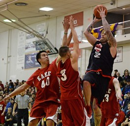 Hoonah's Jonathan Torres (32) shoots over Kake's Shawn Jackson (40) and Tim Demmert (3) in their B-Bracket game of the Juneau-Lions Club 71st Annual Gold Medal Basketball Tournament at Juneau-Douglas High School on Monday. Hoonah won 61-57. (Photo courtesy Klas Stolpe)