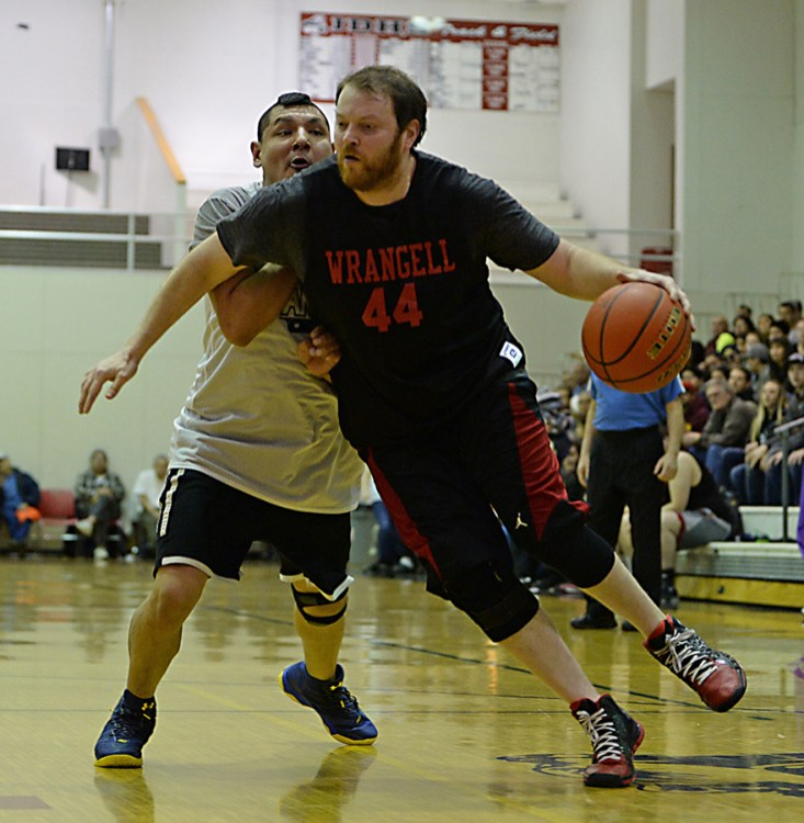 Wrangell's Jason Clark (44) drives against Angoon's Dustin Endicott during their B-Bracket elimination game in the Juneau Lions Club 71st Annual Gold Medal Basketball Tournament at Juneau-Douglas High School on Thursday. Wrangell won 92-81. (Photo courtesy Klas Stolpe)
