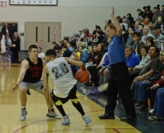 Wrangell's Andrew Versteeg (33) defends Angoon's Clayton Edwin (20) during their B-Bracket elimination game in the Juneau Lions Club 71st Annual Gold Medal Basketball Tournament at Juneau-Douglas High School on Thursday. Wrangell won 92-81. (Photo courtesy Klas Stolpe)