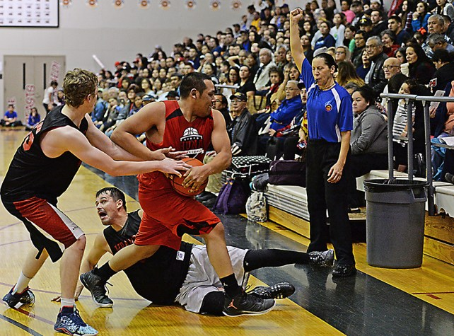 Referee Suzanne DePoe calls a foul as Wrangell's Robbie Marshall and Tony Harding tie up Hoonah's Jaylin Prince during their B-Bracket elimination game in the Juneau Lions Club 71st Annual Gold Medal Basketball Tournament at Juneau-Douglas High School on Friday. Hoonah won 85-77. (Photo courtesy Klas Stolpe)