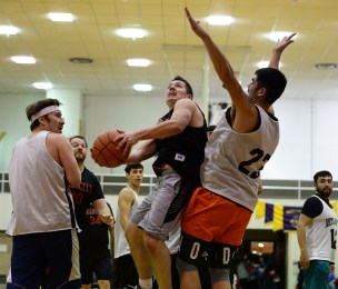 Wrangell's Andrew Versteeg scores against Metlakatla's Franklin Hayward (23) in B-bracket action at the Juneau Lions Club 71st Annual Gold Medal Basketball Tournament at JDHS on Sunday, March 19, 2017. Wrangell won 84-81. (Photo courtesy Klas Stolpe)