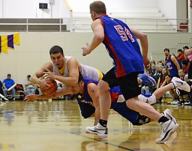 James Gang's Levi Hotch, top, and Filcom's Franz Kugelmann dive for a lose ball during Filcom's 59-51 win in a C Bracket game of the Juneau Lions Club 71st Annual Gold Medal Basketball Tournament at JDHS on Sunday, March 19, 2017. (Photo courtesy Klas Stolpe)