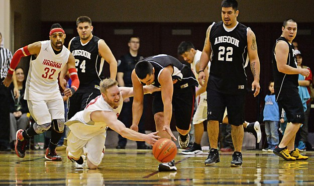 Hoonah and Angoon players go for a loose ball during their C-Bracket elimination game at the Juneau Lions Club 71st Annual Gold Medal Basketball Tournament at Juneau-Douglas High School on Tuesday. Hoonah won 88-66. (Photo courtesy Klas Stolpe)