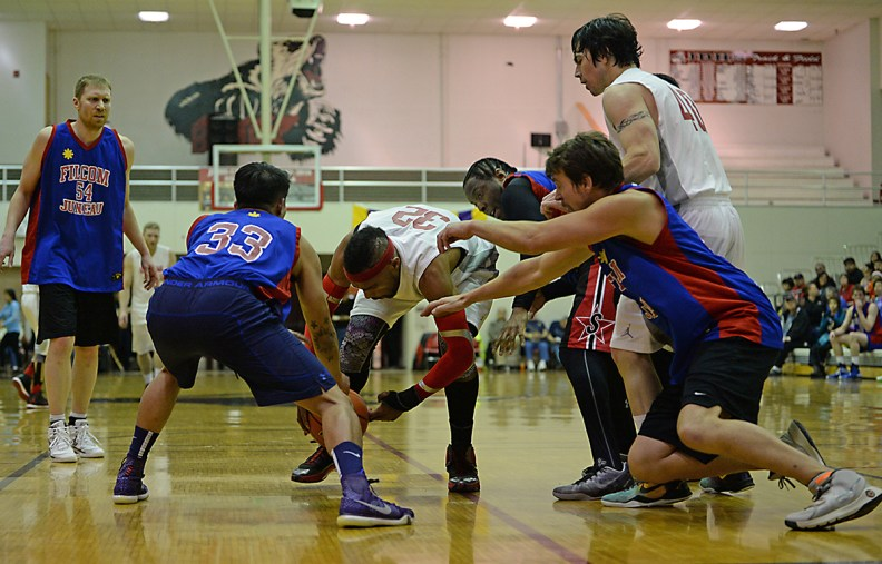 Hoonah's Authur Campbell (32) and Donald Dybdahl (40) battle for a loose ball with Filcom's Ronan Tagsip (33), Rob Ridgeway (4) and Mike Vanderjack during their C-Bracket elimination game in the Juneau Lions Club 71st Annual Gold Medal Basketball Tournament at Juneau-Douglas High School on Wednesday. Hoonah won 66-62. (Photo courtesy Klas Stolpe)
