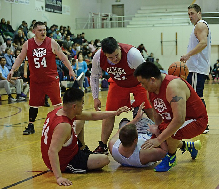 Kake's Thomas Jackson (34), Brandon Jackson (21, and Josh Jackson (33) battle for a loose ball against Juneau James Gang's Ray Zimmer during their C-bracket elimination game at the Juneau Lions Club 71st Annual Gold Medal Basketball Tournament at Juneau-Douglas High School on Tuesday. James Gang won 88-52. (Photo courtesy Klas Stolpe)