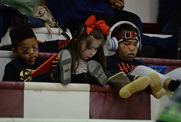 Young fans take an electronic break in the bleachers during the Juneau Lions Club 71st Annual Gold Medal Basketball Tournament at Juneau-Douglas High School on Thursday. (Photo courtesy Klas Stolpe)