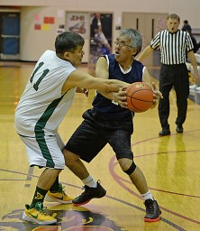 Sitka's Ray Kitka (11) fouls Angoon's Roger Williams (2) during their Masters Bracket game of the Juneau-Lions Club 71st Annual Gold Medal Basketball Tournament at Juneau-Douglas High School on Monday. Angoon won 65-56. (Photo courtesy Klas)
