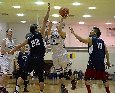 Hoonah's Ed Mercer Jr. (41) scores against Angoon's Edward Jack (22) and Marti Fred (10) during their Masters Bracket elimination game at the Juneau Lions Club 71st Annual Gold Medal Basketball Tournament at Juneau-Douglas High School on Thursday. Hoonah won 94-67. (Photo courtesy Klas Stolpe)