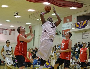 Hoonah's Tierney Bible (50) shoots over Kake's Nick Davis and Lloyd Davis (21) during their Masters Bracket game at the Juneau-Lions Club 71st Annual Gold Medal Basketball Tournament at Juneau-Douglas High School on Monday. Hoonah won 80-66. (Photo courtesy Klas Stolpe)