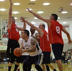 Angoon's Frank Jack is defended by Kake's Lloyd Davis (21), Keith Nelson (10) and Jay Peterson (8) during their Masters Bracket elimination game in the Juneau Lions Club 71st Annual Gold Medal Basketball Tournament at Juneau-Douglas High School on Friday. Kake won 94-67. (Photo courtesy Klas Stolpe)