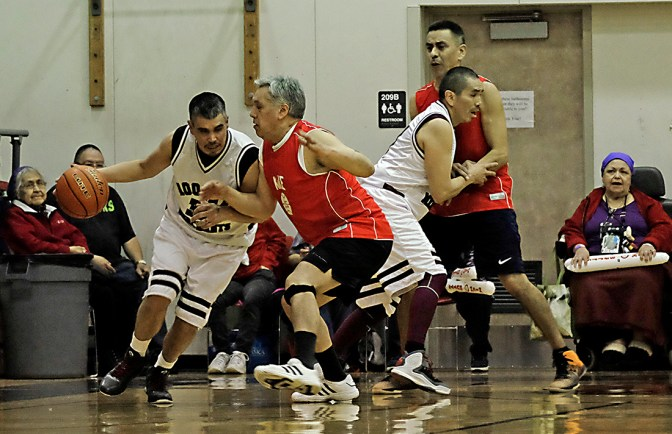 Hoonah's Albert Hinchman dribbles against Kake's Willis Cavanaugh as Hoonah's Louie White screens Kake's Jay Peterson during the Master's Bracket championship of the Juneau Lions Club 71st Annual Gold Medal Basketball Tournament at Juneau-Douglas High School on Saturday. Hoonah won 80-78. (Photo courtesy Klas Stolpe)