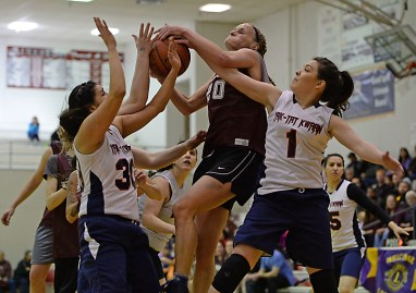 Haines' Sarah Elliott (20) is fouled by Yakutat's Jasmine James (30) and Kaityln Ivers (1) during their Womens Bracket semifinal in the Juneau Lions Club 71st Annual Gold Medal Basketball Tournament at Juneau-Douglas High School on Thursday. Haines won 65-52. (Photo courtesy Klas Stolpe)
