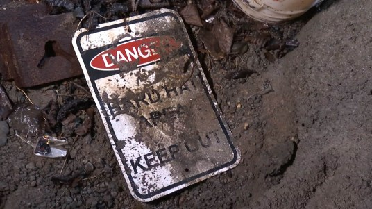 An old safety sign lies in the dirt on the floor of the old tunnel under Telephone Hill (Video still by David Purdy/KTOO)