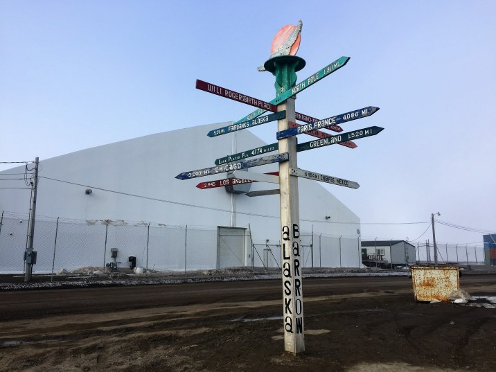 A mile post close to the airport in Utqiaġvik. It's one of many visible ways that the transition from the name 'Barrow,' is still ongoing. (Photo by Ravenna Koenig/ Alaska's Energy Desk.)