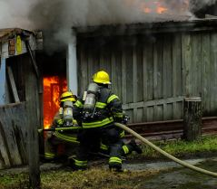 Capital City Fire/Rescue firefighters enter the Thane Ore House and attack an interior fire during the controlled burn on Nov. 24, 2018.