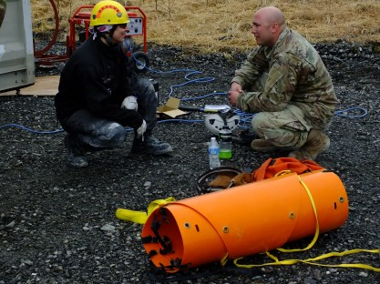 Meghan Desloover of Capital City/Fire Rescue chats with Tech Sgt. Derek Reese of Washington National Guard as he takes a break from jackhammer work during an urban search and rescue exercise in Juneau on April 12, 2019.