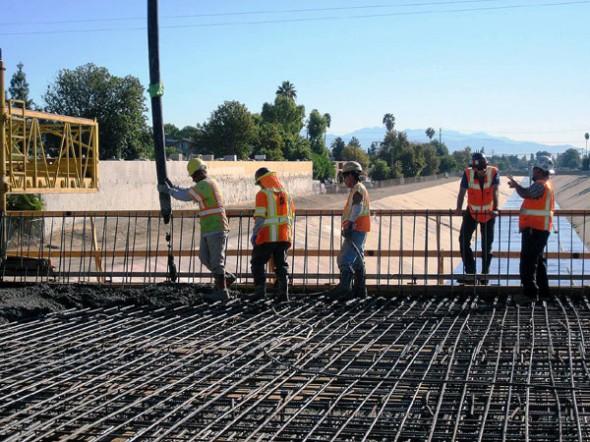 Trabajadores de la construcción ponen el concreto de lo que será la superficie del puente del río de Los Ángeles, parte de la extensión Canoga de la Línea Naranja del Metro. Foto Perla Berry/Metro.