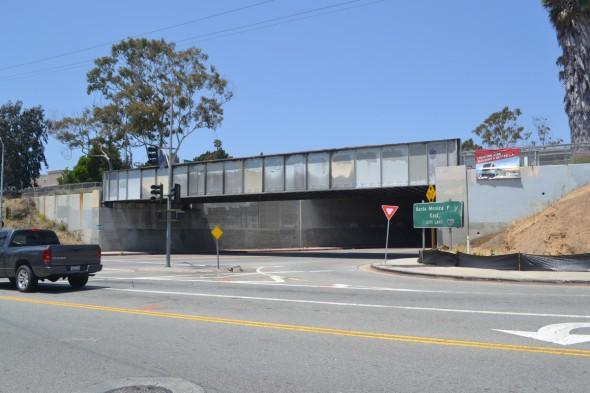 El puente original de ferrocarril que cruza National Blvd., está próximo a la futura estación Palms. El cartel de la derecha pregona que el proyecto de la Medida R está invirtiendo el dinero de los contribuyentes del Condado de Los Ángeles en forma correcta. Foto Carter Rubin/Metro.