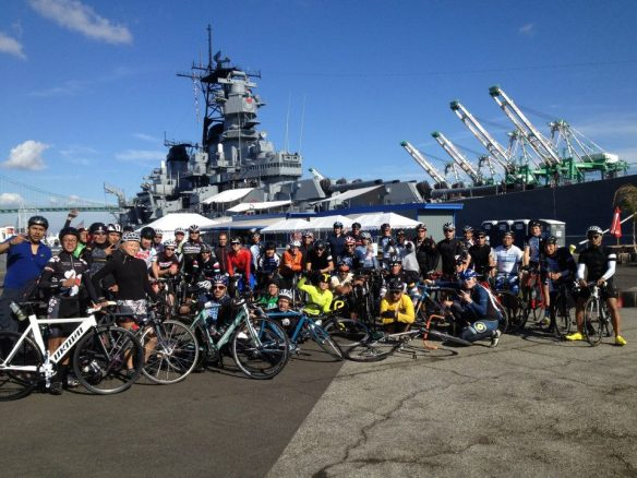 Ciclistas posando frente al USS Iowa.