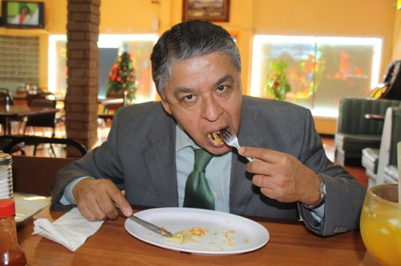 """Carlos Serrano atrapado en el momento de """"ataque"""" contra una pupusa de camarón con queso. (Foto de Agustín Durán/El Pasajero)."""