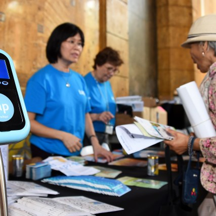 Visitor-with-TAP-card-demonstration-tool-at-Metro-First-older-Adult-Transportation-Expo